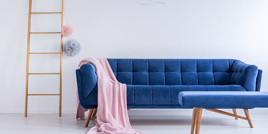 Blue Velvet Couch with Pink Blanket and Decorative Ladder in White Room