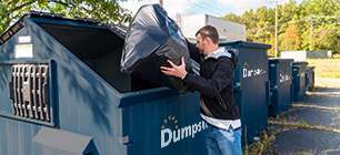 Business owner tossing trash in Dumpsters.com front load dumpster.