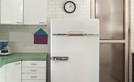 White Refrigerator and Freezer Next to Green Counter and White Cabinets