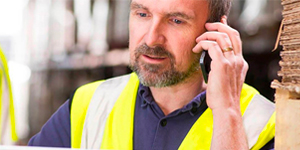 A Man in a Yellow Work Vest on the Phone.