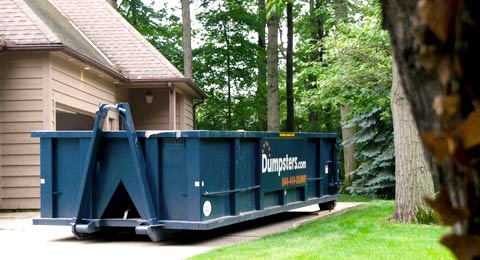 Roll Off Dumpster in Driveway Surrounded by Trees.