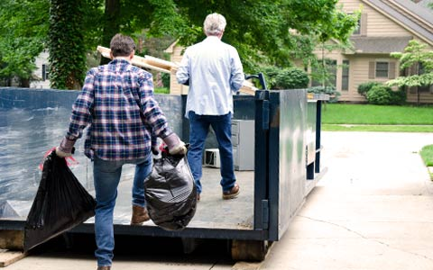 Two Men Loading Household Trash Into a Roll Off Dumpster.