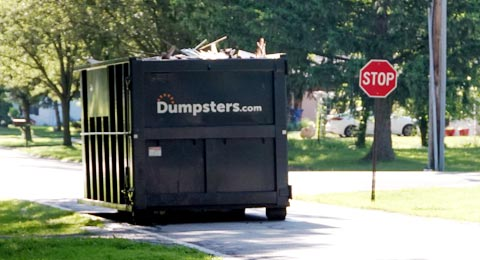 A Full Dumpsters.com Roll Off Dumpster in a Street Near a Stop Sign.
