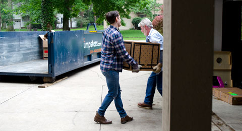 Two Men Loading a Box into a Blue Roll Off Dumpster.