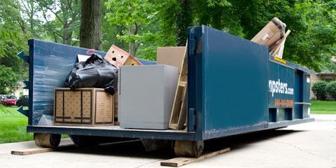 Blue Roll Off Dumpster Filled With Debris From Junk Removal Project.