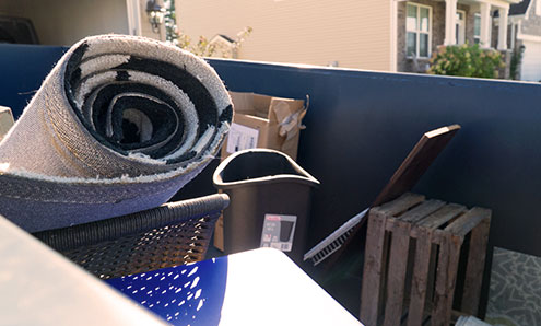 Overhead Shot of Household Junk in a Blue 10 Yard Dumpster