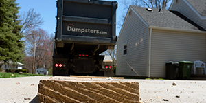 Debris on the Ground in the Foreground While a Dumpsters.com Truck Backs Up Into a Driveway