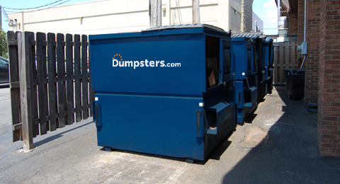 A Blue Front Load Dumpster in an Enclosure.