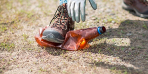 boot crushing a brown plastic bottle