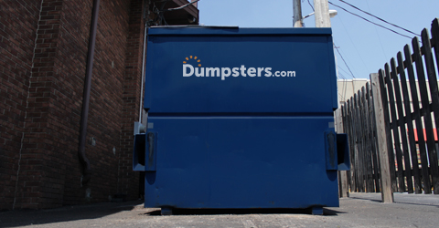 Front Load Dumpster Sitting in an Alley Outside a Building