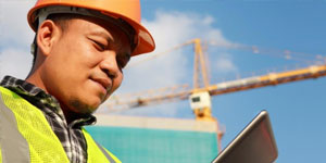 Construction Engineer Looking at an iPad With a Crane in the Background