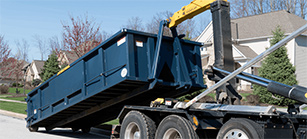 A Roll Off Dumpster is Placed on the Ground by a Truck.