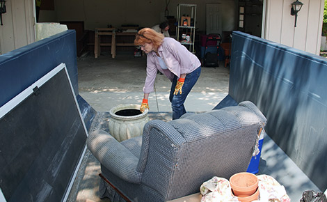 woman throwing old furniture in a dumpster