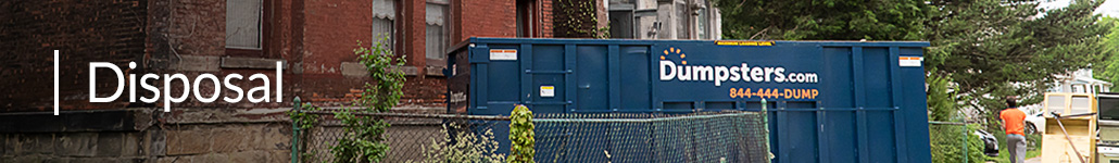 A Roll Off Dumpster Outside of a Brick House