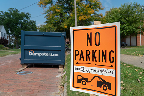 a sign that says no parking next to a dumpsters.com container