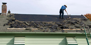 Roofer Scraping Shingles Off the Roof