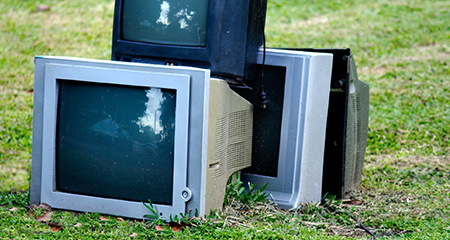 A Pile of Televisions on a Lawn.