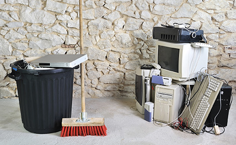 a pile of computer equipment next to a trash can