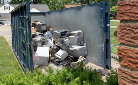 a pile of e-waste in a roll off dumpster