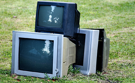A Pile of Televisions on a Tree Lawn.