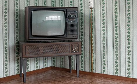 A TV on a Table in a Corner.