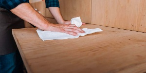 Man cleaning wood table with cloth.