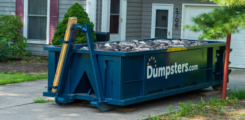 roll off dumpster in driveway filled with concrete