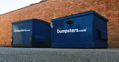 two front load dumpsters against a brick wall