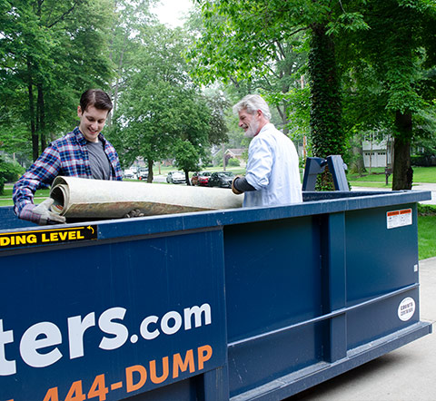 Two Men Filling Small Roll Off Dumpster With Junk.