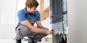 Man in Blue Shirt Fixing Appliance.