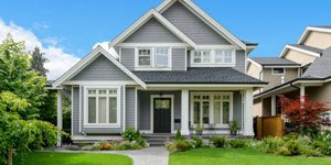 Beautiful Gray Home With Blue Skies and Green Grass.