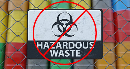 A No Hazardous Waste Sign on a Fence Containing Industrial Drums.
