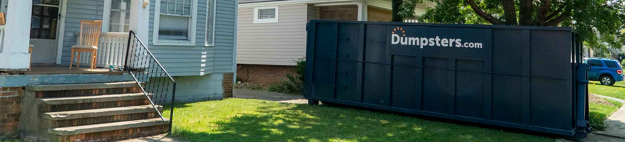 A Roll Off Dumpster in a Residential Driveway Near a Blue House.