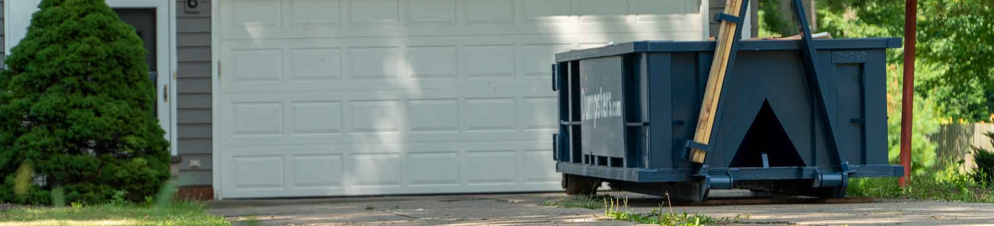 Blue Roll Off Dumpster in a Driveway in Front of a Closed White Garage Door.