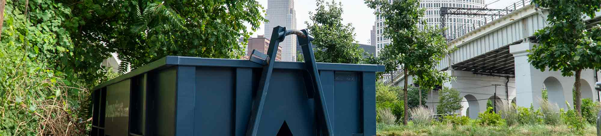 Blue Roll Off Dumpster With Cleveland Skyline in the Background.