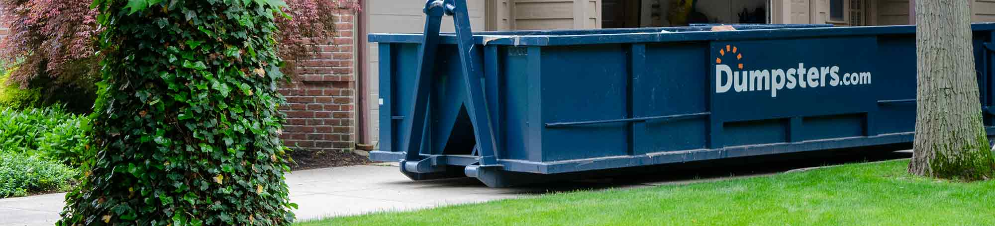 A Blue Roll Off Dumpster in the Driveway Outside of a Garage.