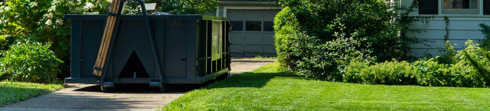Blue Roll Off Dumpster in Driveway of White House With Green Lawn.