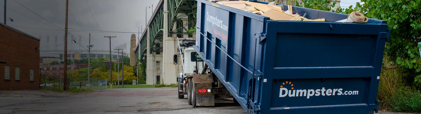 Remodeling Debris in a Dumpsters.com Roll Off Dumpster with the Lorain-Carnegie Bridge and Progressive Field in the Background.