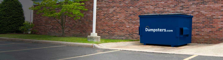 business dumpster rental next to a brick wall