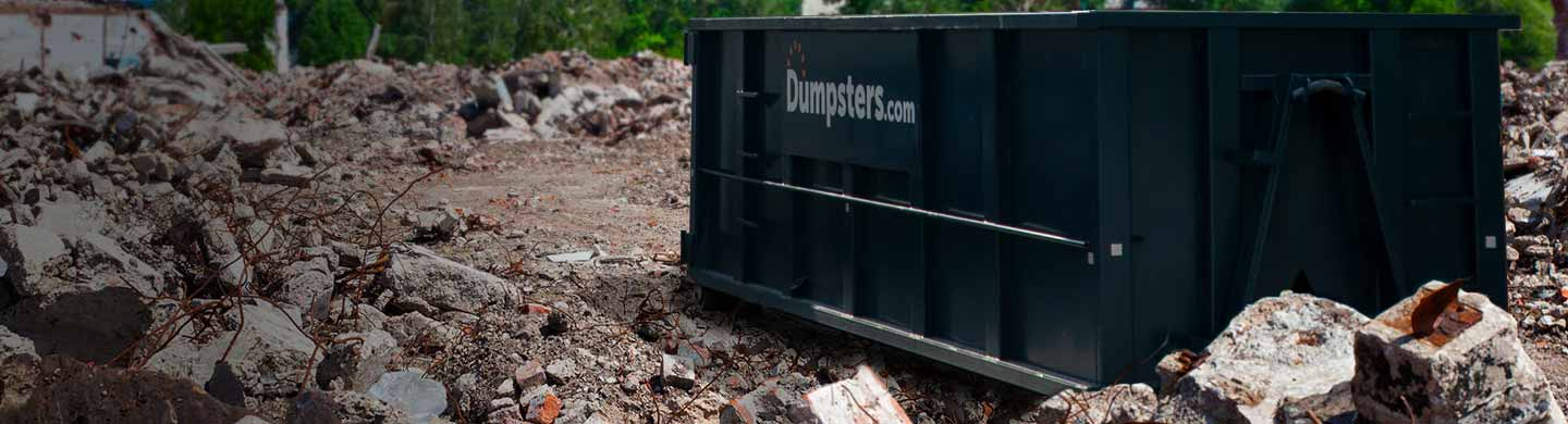 roll off dumpster surrounded by piles of concrete debris