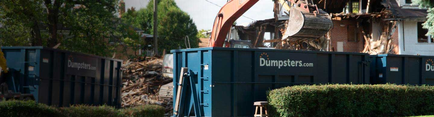 Roll Off Dumpsters Surrounded by Construction Material and Equipment