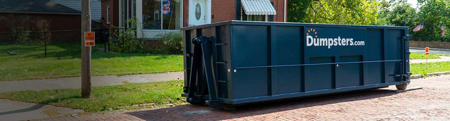 Blue 30 Yard Dumpsters With Dumpsters.com Logo Outside of Home