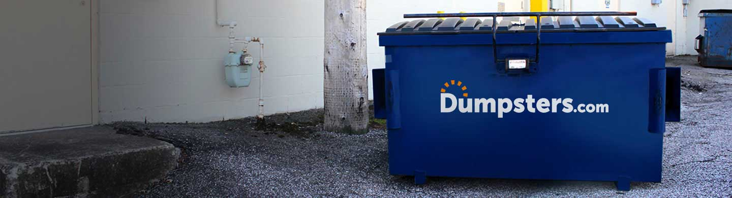 4 Yard Dumpster With Dumpsters.com Logo in Parking Lot in Front of Fence