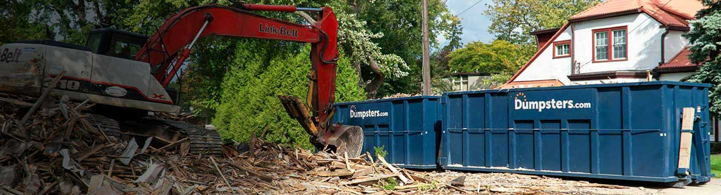Two Blue 40 Yard Dumpsters With Dumpsters.com Logos Next to Construction Debris and Equipment