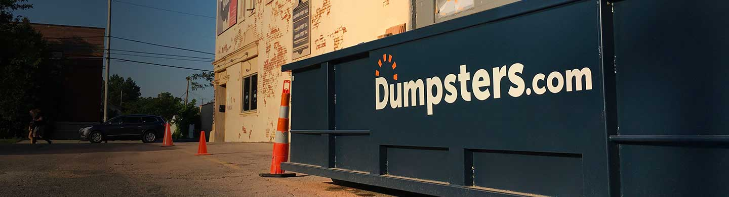 dumpster placed on a street surrounded by orange cones