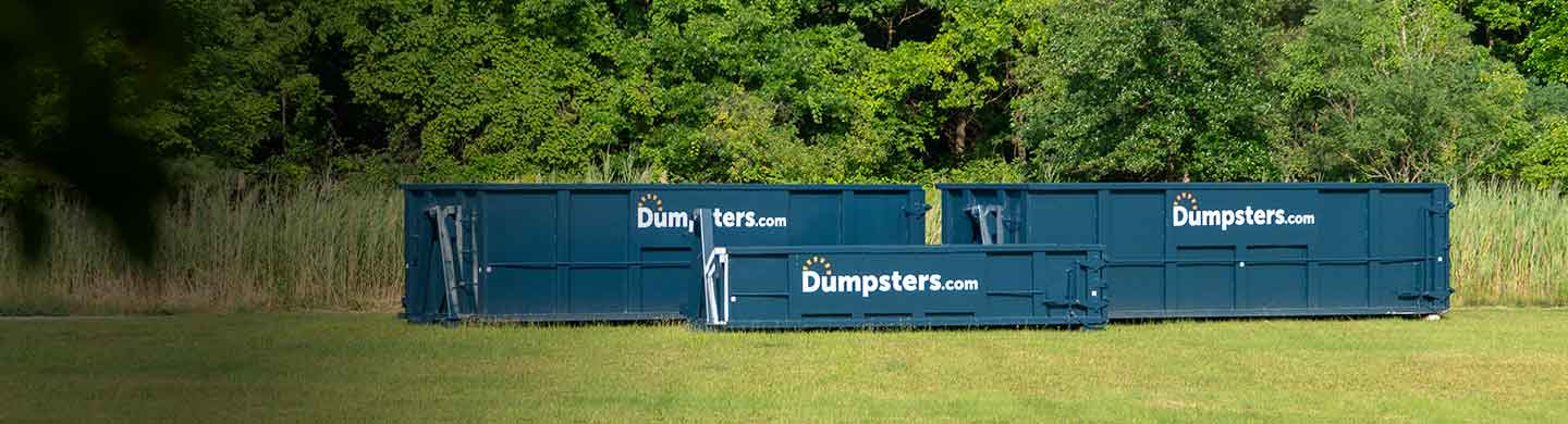 three dumpsters of various sizes in a field