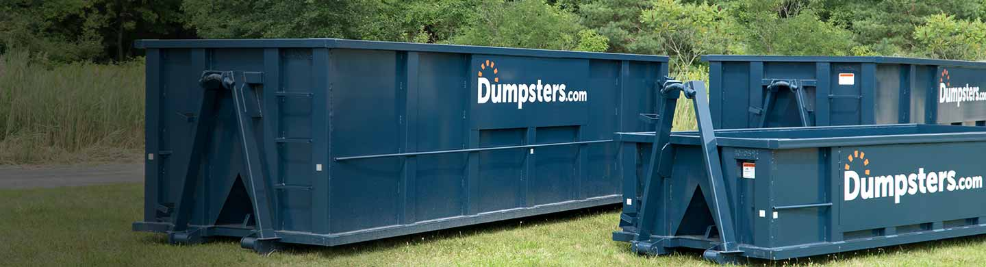 various dumpster sizes in grassy field