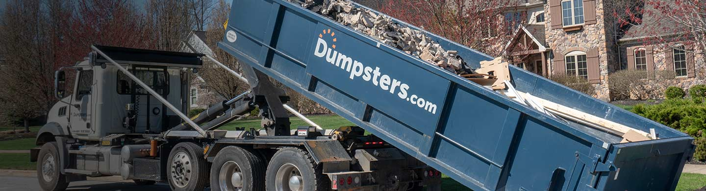 A Dumpsters.com Roll Off Dumpster Filled With Heavy Debris Being Loaded Onto a Truck.