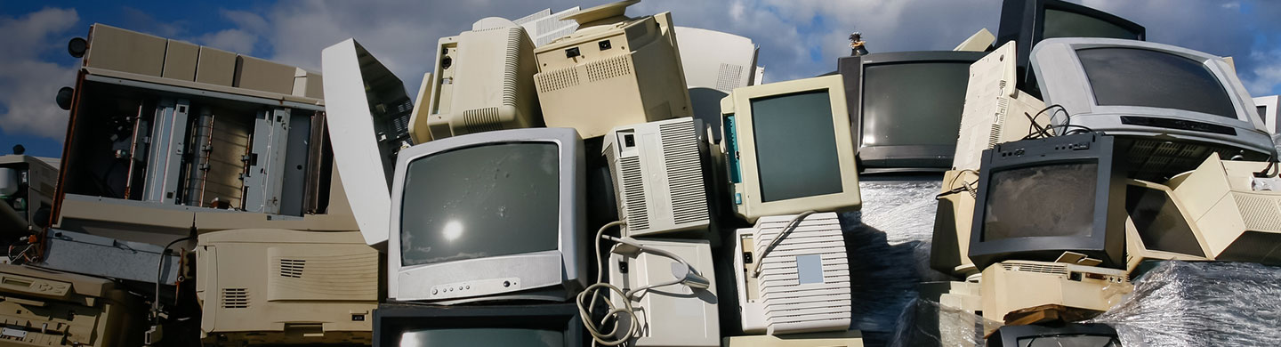 a pile of tube televisions and computer monitors