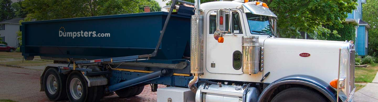 truck with dumpster in driveway